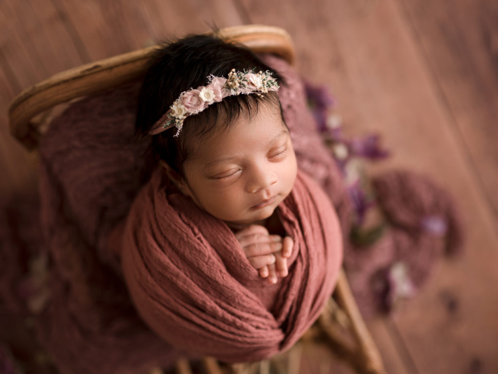 Newborn Baby Photographer, sleeping newborn baby girl with pink blanket and floral headband