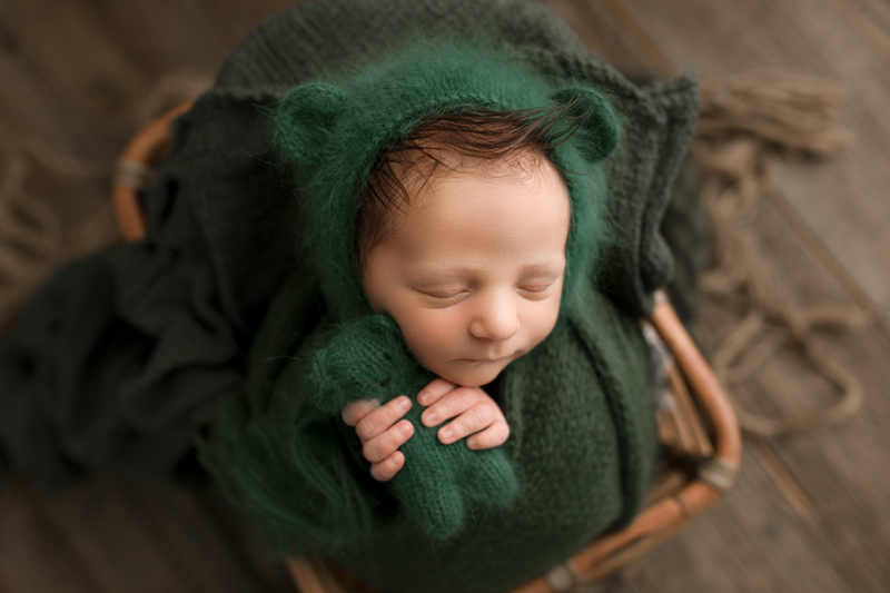 Newborn Photographer, Sleeping newborn comfy in basket wrapped in green blanket